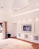 White, designer bedroom with indirect lighting in wall