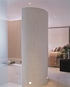 Curved partition around bathtub in open-plan, designer bedroom