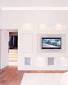 Modern bedroom with flat-screen TV integrated into wall and open door leading to dressing room