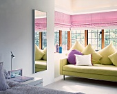 Modern sofa with scatter cushions in glazed bay window of bedroom