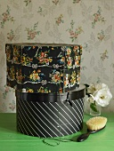 Two hatboxes on table in front of floral wallpaper