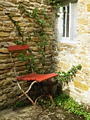 Rusty, old chair next to wall in corner of garden