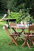 Set table in garden with chairs & barbecue in background