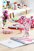 Various pink writing materials on table