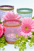 Various tea light holders decorated with flowers