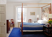 Bedroom with canopied bed, blue bedspread & blue rug