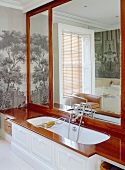Bathtub with wooden surround in front of large mirror & pictorial wallpaper