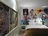 Printed sliding panels in wooden frame and mural behind double bed in retro hotel room