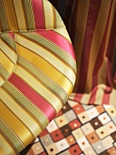 Colourful mix of patterns on chair upholstery, carpet and curtain