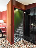 Wild mix of patterns on carpet, wallpaper and stair carpet contrasting with black-lacquer door element and retro chair