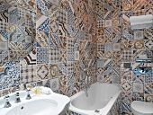 Traditional hotel bathroom with floor-to-ceiling tiling in unconventional mix of patterns