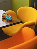 Small table in a bar with bright orange and yellow, retro-style shell chairs