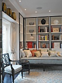 Classic, modern seating corner with vases and books in fitted shelving
