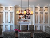 Modern dining area and classic fitted cupboards with fabric panels in doors