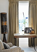 Small desk below window with traditional curtains and Africa-style standard lamp