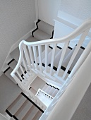 Traditional wooden stairs in stairwell with grey and black stair runner