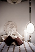 Antique-style white plaster relief and egg-shaped porthole behind bed with scatter cushions and bedspread in natural shades
