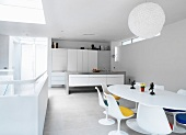 Open-plan room with minimalist kitchen and white dining area in designer retro style