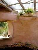 Organisch geformtes Lehmhaus mit einfacher Oberlichtkonstruktion und Buddha-Statue in der rahmenlosen Fensteröffnung