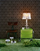 Wallpaper with traditional pattern as backdrop for acrylic glass lamp on modern, grass green, Italian designer cabinet with castors