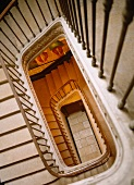 View down through rectangular stairwell with delicate metal balustrade in historic building