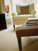 Light, upholstered armchair on castors with circle-patterned cushion in elegant contemporary living room