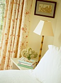 Bedside lamp with slender bamboo base in corner of romantic bedroom