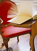 Antique ensemble of desk and chair with red upholstery and book with riffling pages