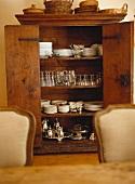 Porcelain and silverware in antique wooden cupboard with open doors