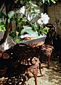 Small seating area on terrace with antique-style metal furniture and simple wooden tray