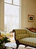 Antique recamier with carved wooden frame and checked upholstery in traditional, sunny apartment in period property