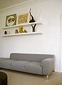 Shelves with objet d'art and pictures above plain, grey recamier