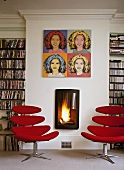 Library with red, modern swivel chairs and pop art pictures above burning open fire