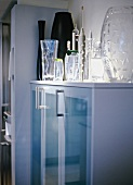 Modern kitchen cupboard with glass doors, spotlights on collection of glass vases