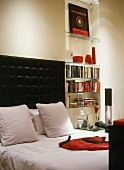 Stylish black and white room with red accessories - glass shelves in niche and double bed with cushioned headboard