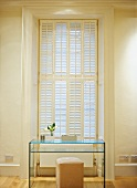 Simple, glass desk with shelf and leather stool in front of closed window shutters in high-ceilinged room in old building