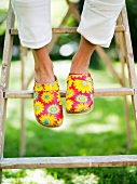 Feet in clogs with cheerful floral pattern