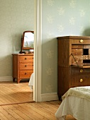 Antique chest of drawers with mirror and antique bureau in two rooms with floral wallpaper