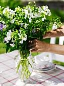 Woman arranging bouquet in glass vase