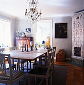 Candlesticks on plain wooden table and white-painted chairs in rustic dining room