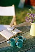 Ornamental miniature watering cans and open book on table
