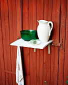 Still-life of washing utensils on shelf mounted on rust-red wall of house