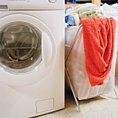 Laundry basket filled with washing next to a washing machine