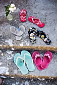 Assorted pairs flip flops on a mossy stone floor