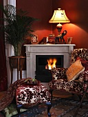Antique chair with matching stool in front of a fireplace and blazing fire