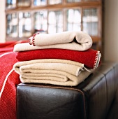 Stack of bedspreads on a black leather bench