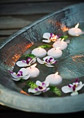 Floating, flaming tea lights in a metal bowl