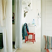 A red lacquered kitchen chair with a jacket hanging over the back next to a hallway with a white curtain