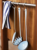 Vintage white enamelled kitchen utensils hanging on hooks on a wooden wall