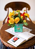 Yellow and red flowers in a ceramic pot on an antique wooden side table